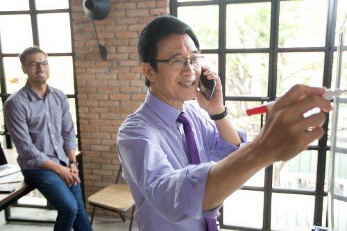 Older asian businessman on mobile for blog post