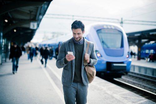 Man looking at mobile walking on train platform for blog post